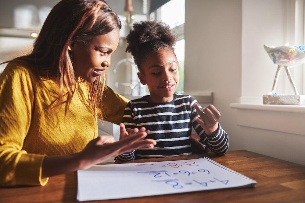 Happy young girl learning to calculate with mother at home, black woman and child