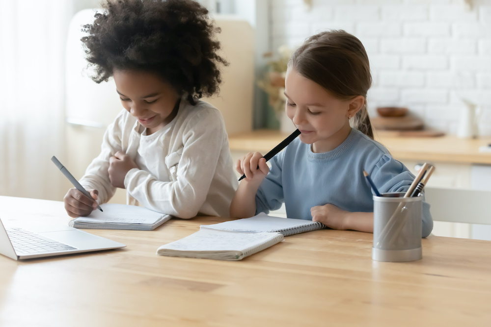 Two girls doing writing homework  at home. Holding felt-tip pens writing essay on workbook, thinking on common task. Completing lessons that create confident writers in the classroom or through online writing lessons. Back to school writing unit