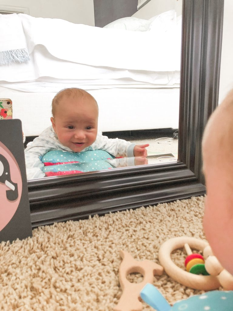 baby doing tummy time in front of a mirror to support your 3-month-old's development