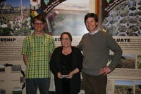 Peggy Olwell (center) is presented with IAE's 2013 Ecological Conservation Award by Rob Fiegener (left) and Tom Kaye (right).