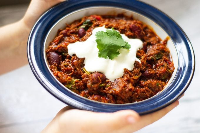 Slow Cooker Chilli Con Carne in a bowl with sour cream and coriander leaves