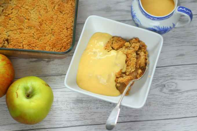 apple crumble with custard in a bowl with cooking apples and a jug of custard nearby.