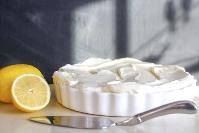 no bake lemon cheesecake with lemons and a serving slice by the side