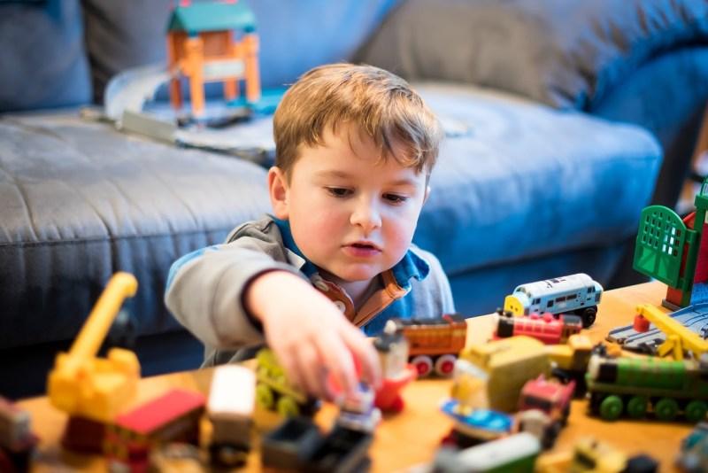 Jeune enfant jouant aux petites voitures