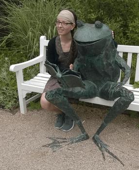 Grenouille en train de lire sur un banc
