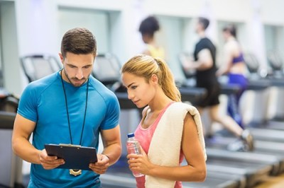 Fitness instructor with a client in a gym