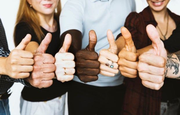 Group of people thumps up agreement support together