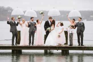 gente con paraguas viendo como los novios se besan.