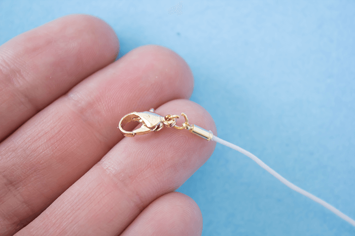 Attach lobster claw to open jump ring. // DIY a bead necklace using nail polish.