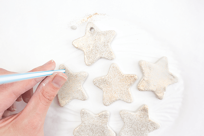 Make a hole at the top of each ornament using a plastic straw.