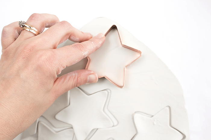 Press cookie cutters into air dry clay.