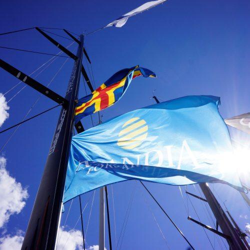 Mast på segelbåt med Alandias flagga vajandes i solskenet, nedanför åländska flaggan.