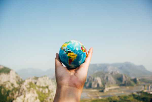 person holding world globe facing mountain