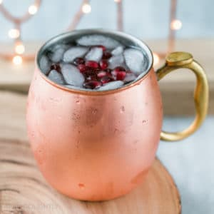 Delicious Pomegranate Moscow Mule Recipe with Pama Liqueur - served in a copper mug with ginger beer, ginger bee, vodka, and pomegranate seeds