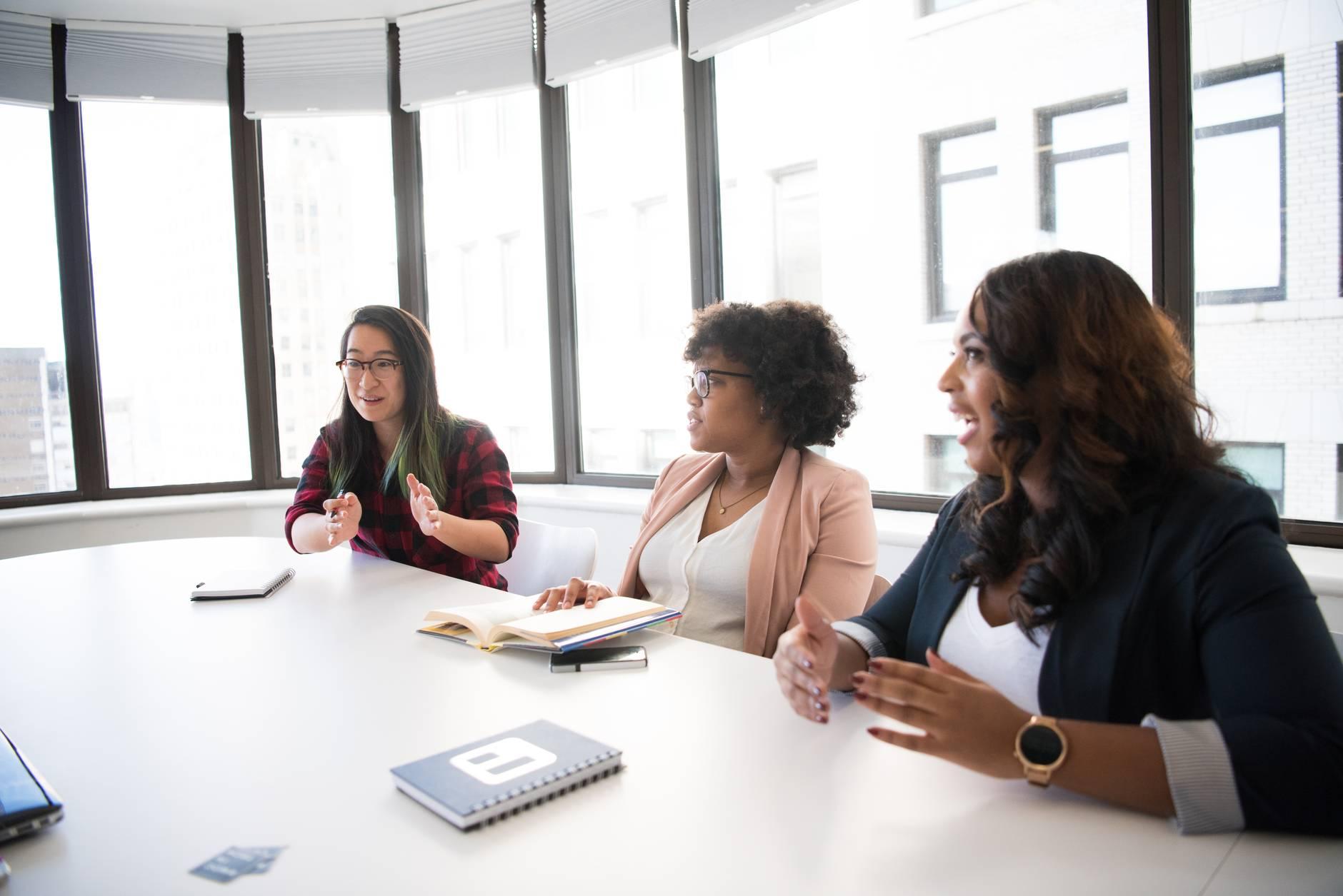 three woman talking near white wooden table inside room