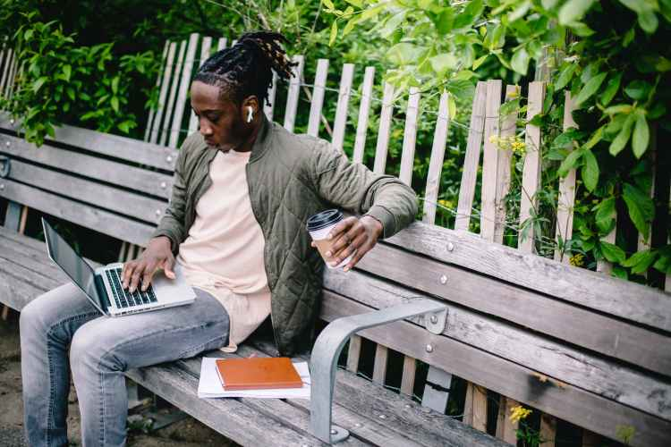 young student with coffee to go using laptop in park