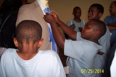 Young men practice tying a tie at the Roundup