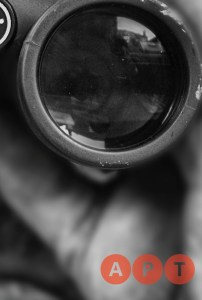 A black and white photo of a person looking through binoculars; the bottom right corner of the photo reads APT