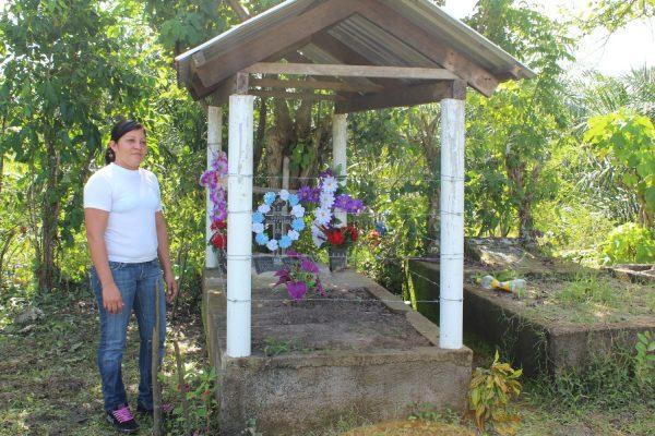 Glenda Chávez, ao lado do túmulo do pai, Gregorio Cháves, cujo corpo foi encontrado em um latifúndio de Dinant em Paso Aguán.