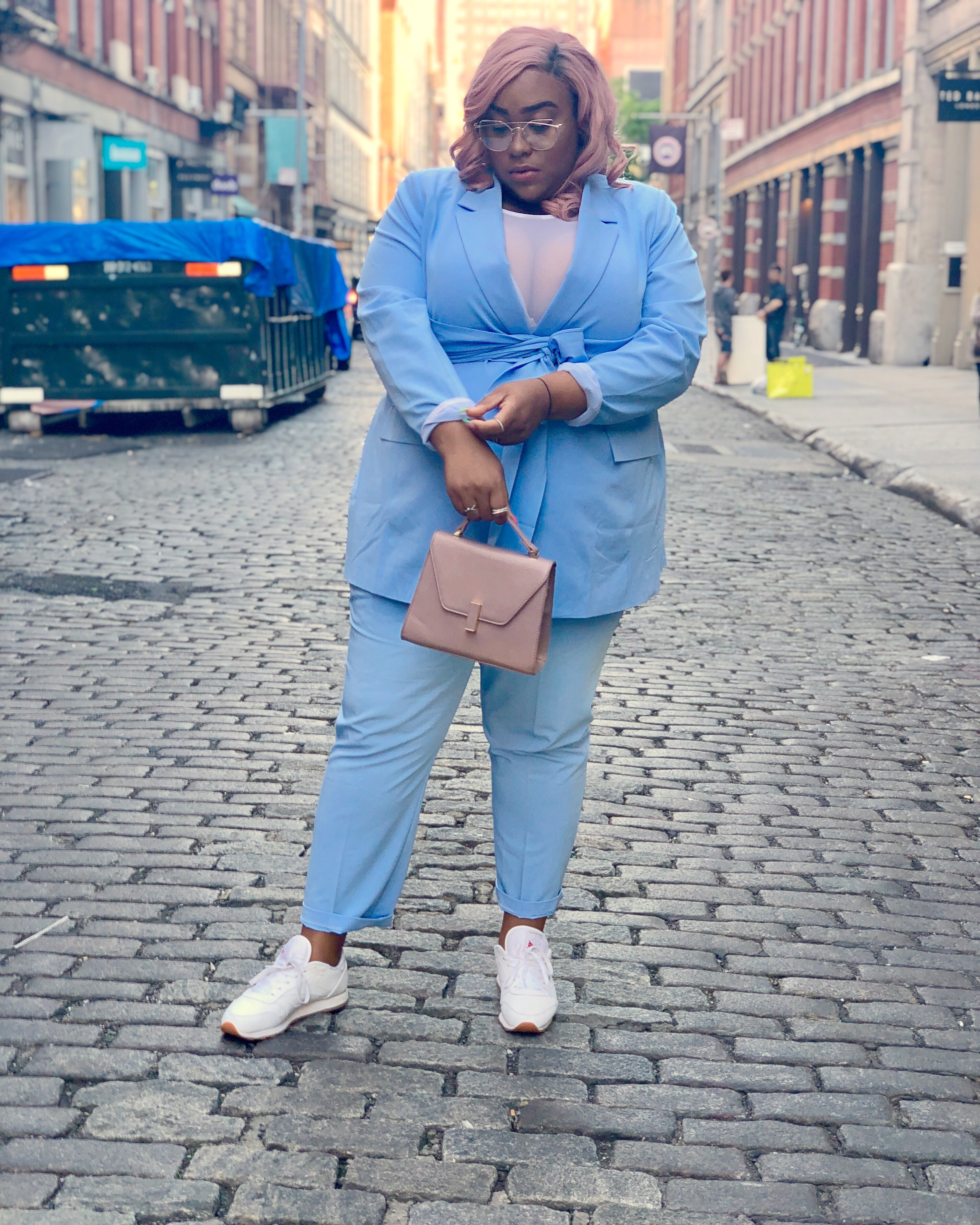 woman of african american descent in a two piece powder blue blazer and pant set. She is wearing white sneakers and has pink hair and wearing glasses