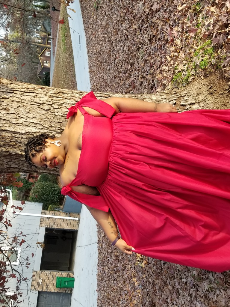 AP smiling standing in front of a tree in a red gown looking towards the ground. Leaves are covering the ground.