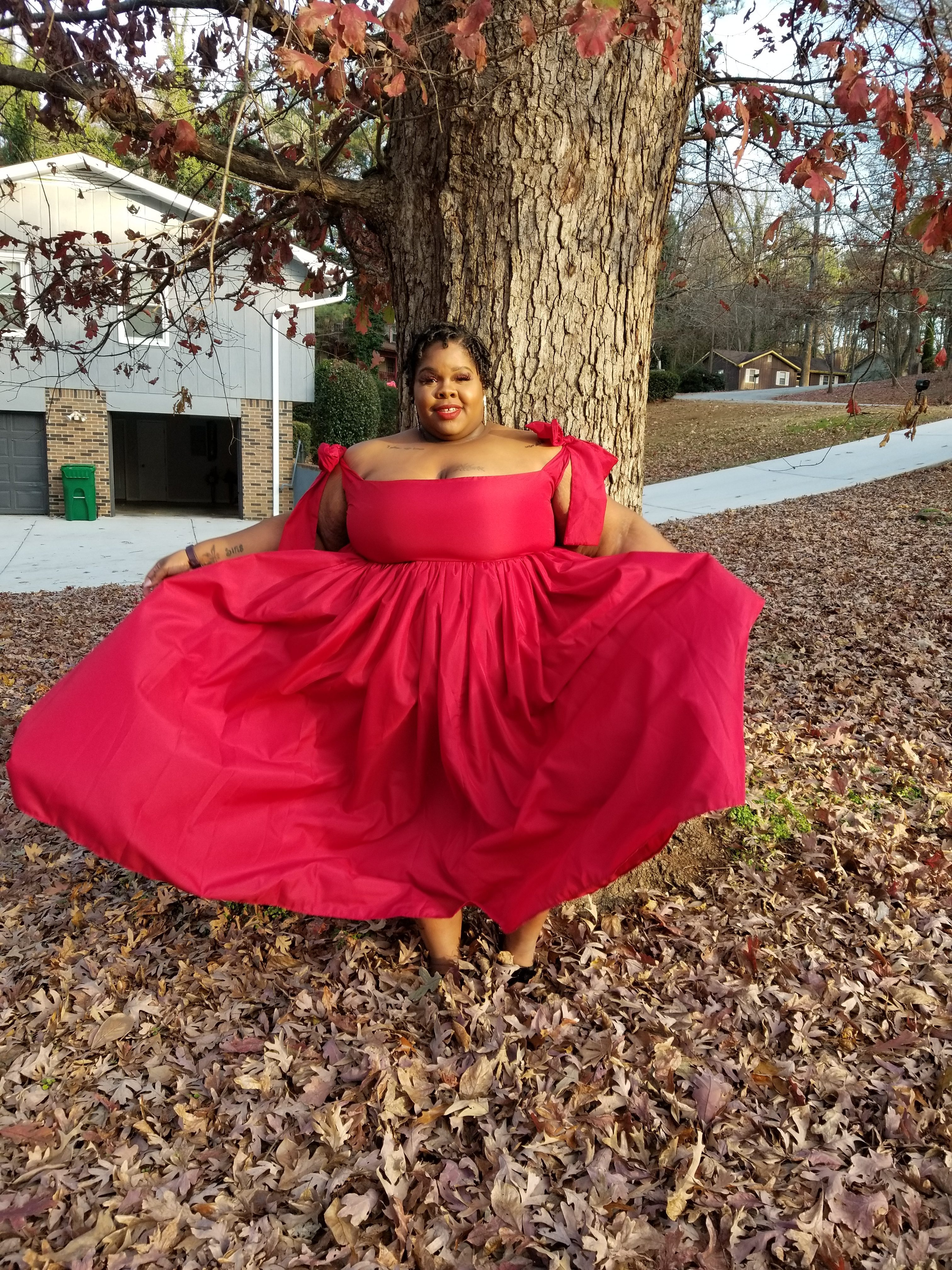 AP smiling standing in front of a tree in a red gown billowing up looking towards the camera. Leaves are covering the ground.