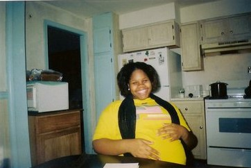 Teen mom, African American seated at a kitchen table holding belly and smiling.