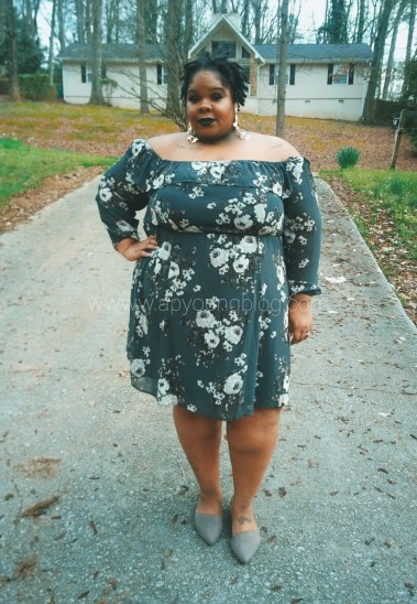 Black plus size woman in an off the shoulder hunter green dress with ivory floral pattern.