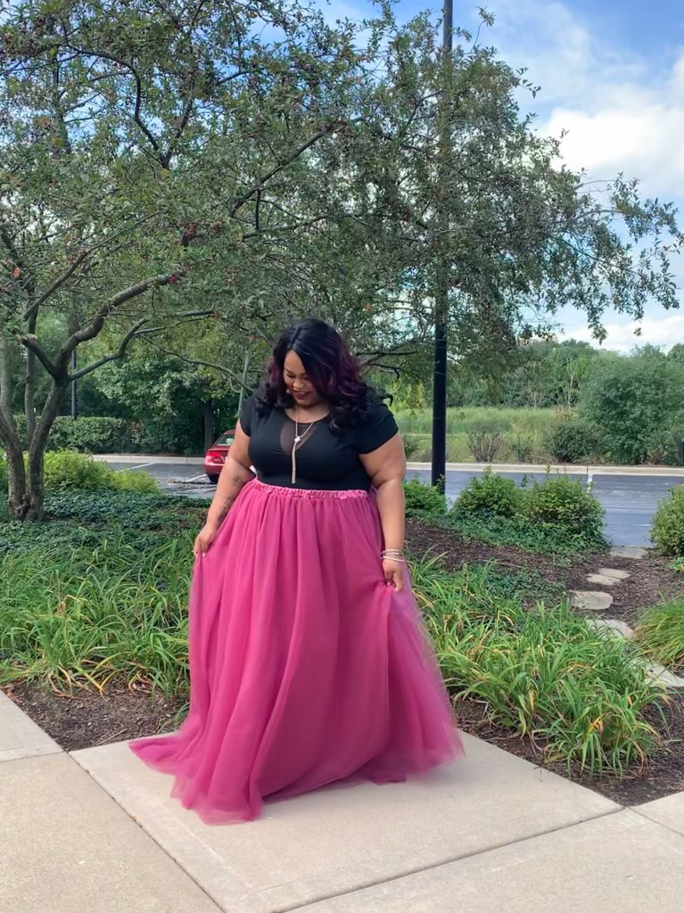 Plus size African American woman wearing a black blouse and magenta long tulle tutu skirt. Her head is downward with a smile. She is discussing mental health in this article.