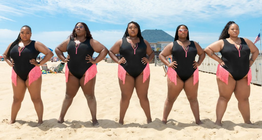 Five plus size black women with varying sizes and body shapes wearing a black bathing suit with a pink zipper detailing down the front and matching pink fringe along the hip line.