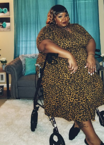 Black plus size woman seated on a rollator wearing leopard print dress with a blond and brown wavy bob cut with bangs.