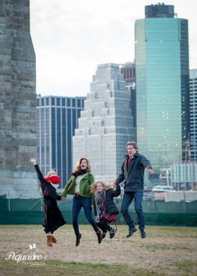 family of four jumps for joy in front of brooklyn bridge