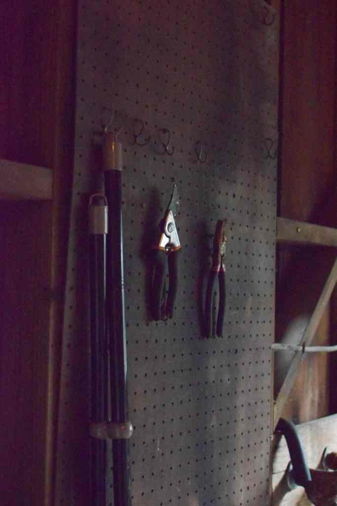 peg board with tools hanging inside a garden shed
