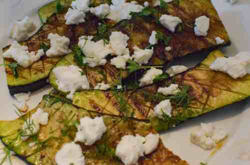 plate of grilled zucchini and topped with goat cheese
