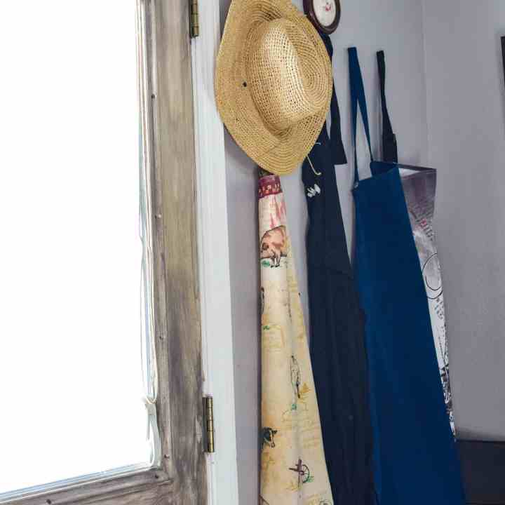 aprons hanging next to a distressed looking door
