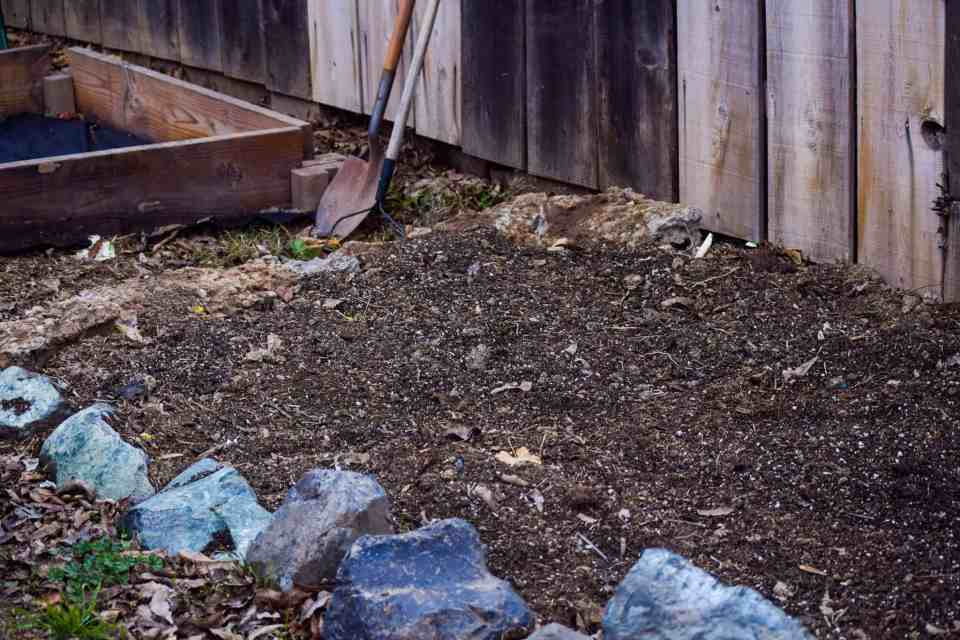 city farm with rock garden bed with dirt filled near urban farmhouse