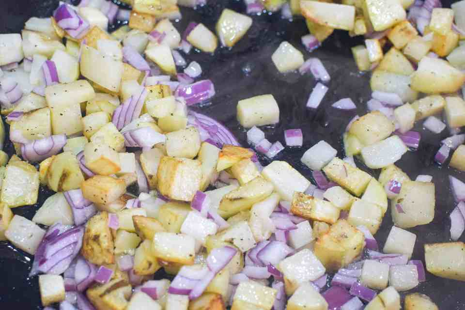 diced potatoes and red onion cooking a skillet