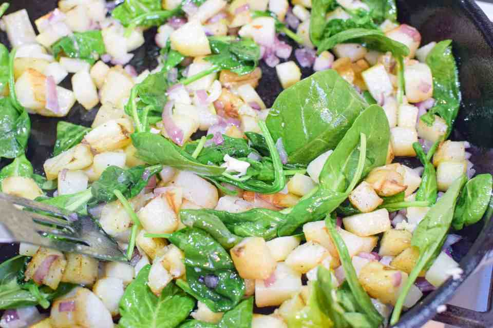skillet with spinach, onions, potatoes cooking