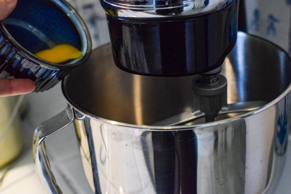 mixer with eggs being poured in to make a classic cheesecake