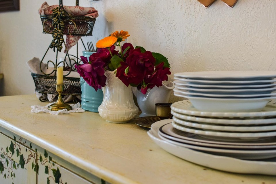 dishes stacked on a vintage tables with flowers in a pitcher giving a french or old world farmhouse look