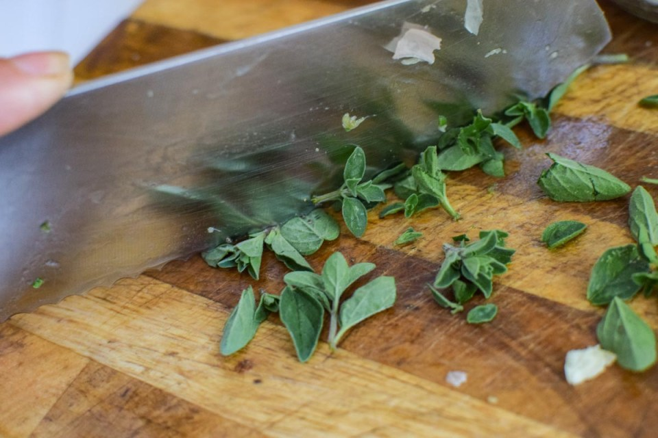 chopping oregano on a cutting board