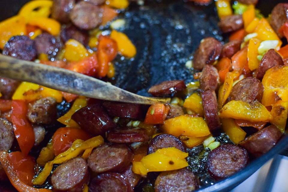 sausages and peppers cooking in a pan