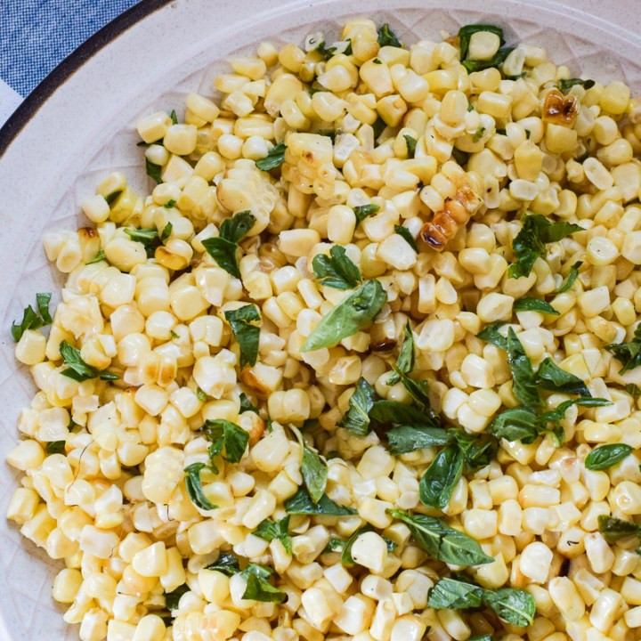 a platter of roasted sweet corn with basil