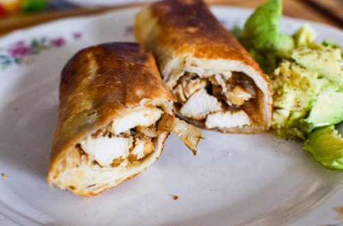 chicken and grilled onion taquitos on a plate