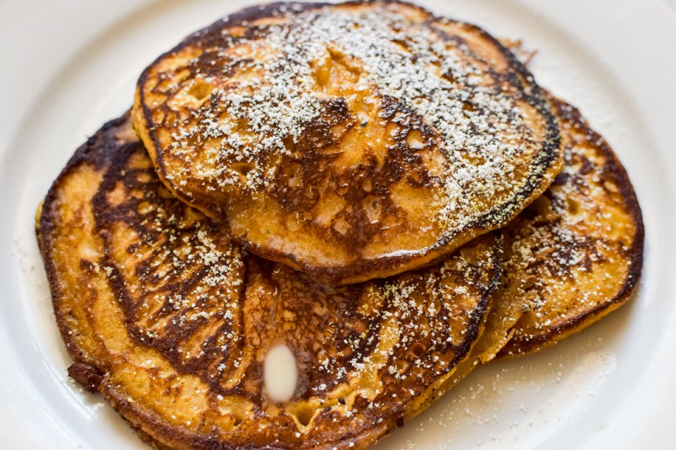 a stack of homemade pumpkin pancakes dusted with powdered sugar