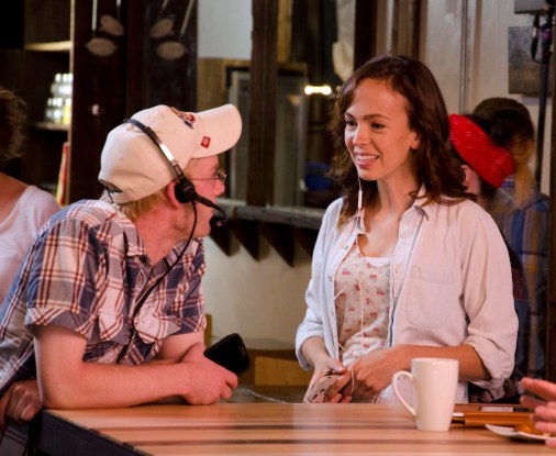 Assistant Director Ryan Port talking with actor Brittany Allen on set.