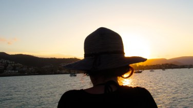 A young woman looks out onto the sunset from a boat, about to dock in the Port of Airlie. Photo by: Leviana Coccia.