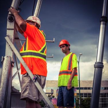 Two men working under a dark sky behind Great West Life. Photo by: Greg Gallinger. @greggallinger/@everydaywinnipeg