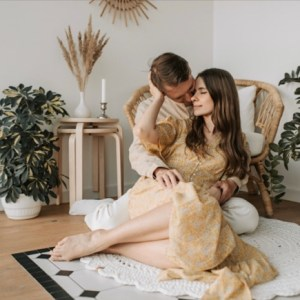 Husband and wife embracing each other while sitting on floor