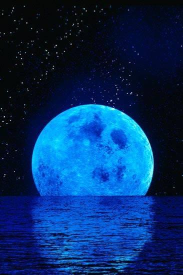 Luna azul poniendose en el mar